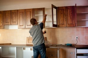 Person working on kitchen cabinets