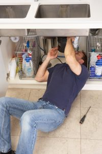 Plumber fixing something under a sink